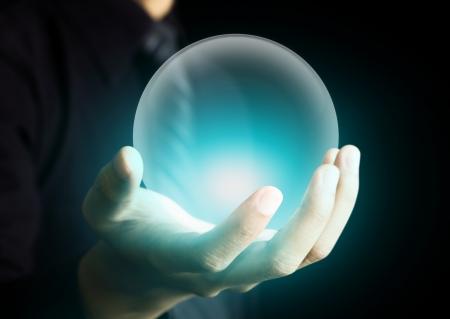 輝く水晶玉を持っている手