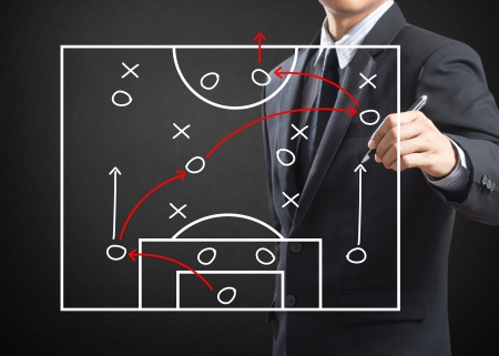 football game: Football coach writing strategy of attacking game