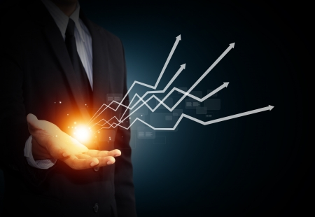 winning stock: Hand holding a rising arrow, representing business growth