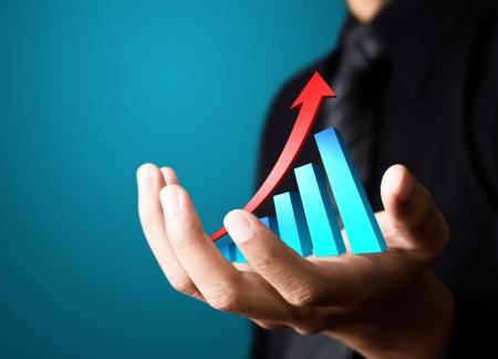Mano che tiene una freccia in aumento, che rappresenta la crescita del business