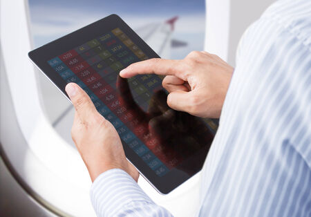 Businessman checking stock market on tablet in airplane photo