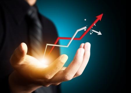 Mano sosteniendo una flecha ascendente, que representa el crecimiento del negocio