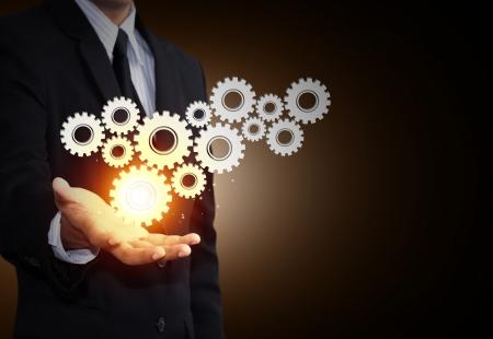 Business man hand show gear to teamwork as concept