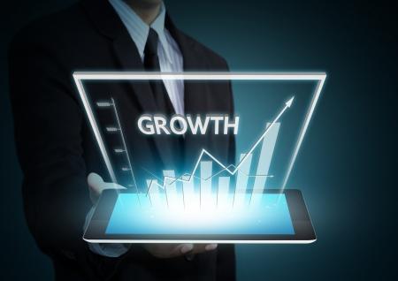 태블릿 기술에 성장 그래프를 들고 비즈니스 손