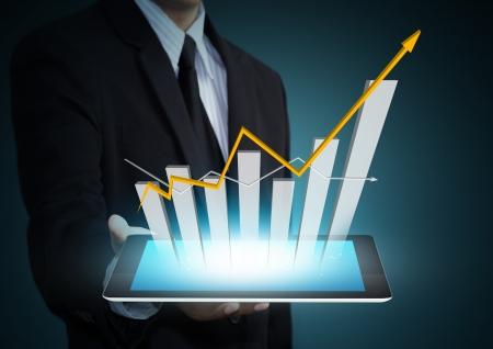 Zakelijke hand met groei grafiek op tablet-technologie Stockfoto