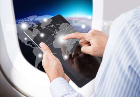 Businessman  in airplane pressing social network and modern communication technology photo