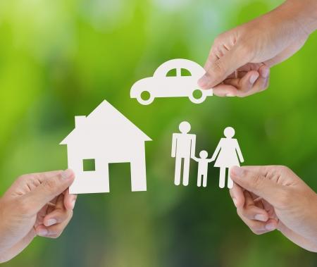 緑色の背景で、保険の概念のペーパー ホーム、自動車、家族を持っている手