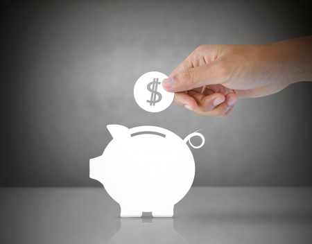 savings and loan crisis: Male hand putting paper coin into a paper piggy bank