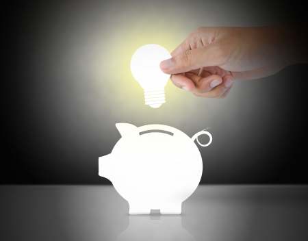 putting: Male hand putting light bulb into a piggy bank, idea concept