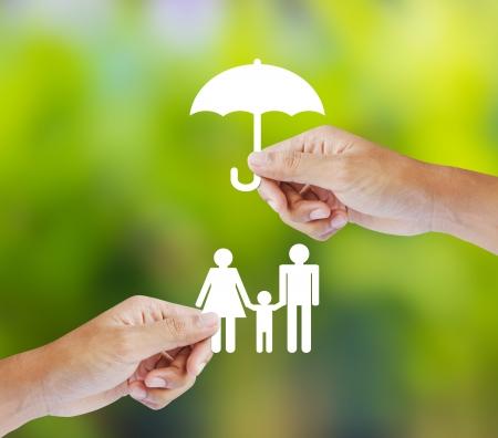 Hand hält ein Papier-Familie und Regenschirm auf grünem Hintergrund