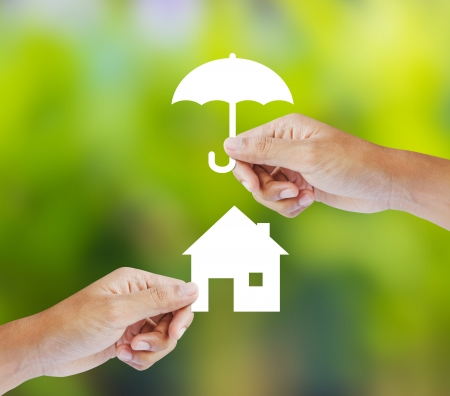 construction management: Hand holding a paper home and umbrella on green background Stock Photo