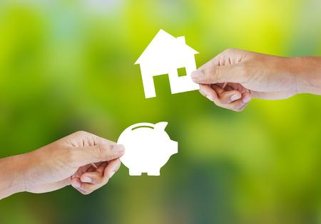 손을 잡고 용지 돼지 저금통 및 집 모양 새 집 구입 개념