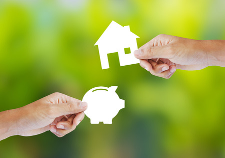 hand holding house: Hand holding paper piggy bank and house shape  New house buy concept