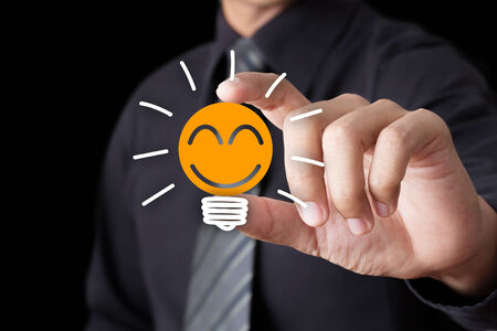 Businessman hand show Light bulb with smile icon, Idea concept photo