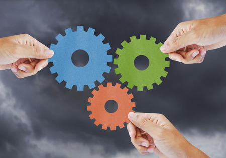Hand show gear to teamwork as concept in storm clouds