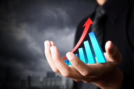 ビジネスの成長を表す上昇の矢印を持っている手