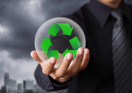 Business people holding recycle sign in crystal ball photo