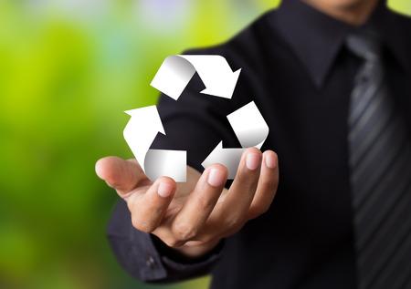 ビジネスの男の手に紙リサイクル サイン
