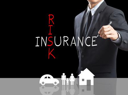 Business man writing Risk Insurance crossword with insurance icon Foto de archivo