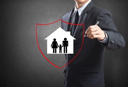 Business man drawing shield protecting family and house, insurance concept