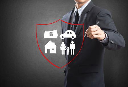 защита: Деловой человек чертеж щит защиты семьи, дом, автомобиль деньги страхования концепции