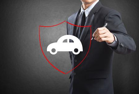 ビジネスの男性を描くシールド保護自動車保険の概念