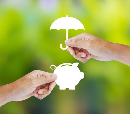 손으로 종이의 돼지 저금통과 우산을 들고, 보험 개념
