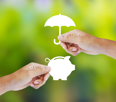 weather protection: Hand holding a paper  piggy bank and umbrella, Insurance concept