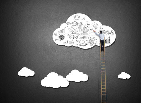 Businessman climbing ladder drawing idea on cloud photo