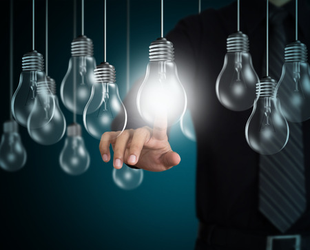 電球、アイデア コンセプトを指してビジネスマン手