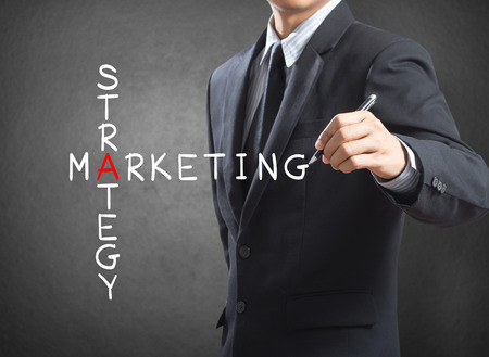Business man writing marketing strategy concept by crossword photo