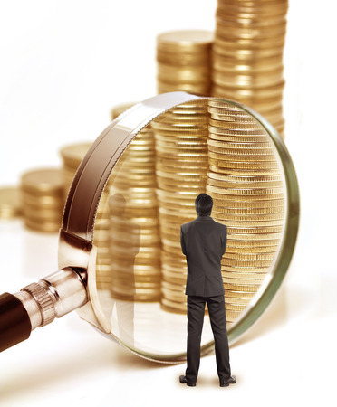 distrust: Businessman checks the money with magnifying glass