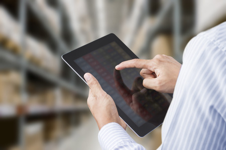 inventories: Businessman checking inventory in stock room of a manufacturing company on touchscreen tablet Stock Photo
