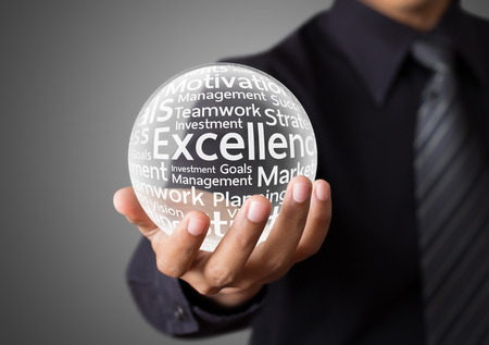 Businessman hand showing excellence word in crystal ball