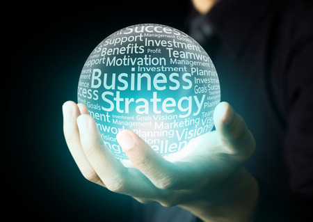 Businessman hand showing business strategy word in crystal ball photo