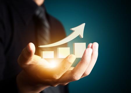 Hand houden van een stijgende pijl, wat neerkomt op groei van de activiteiten. Stockfoto