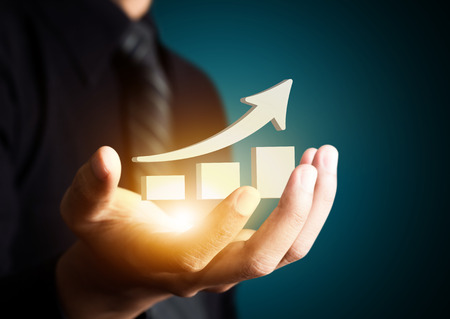 crisis economica: Mano que sostiene una flecha ascendente, lo que representa el crecimiento del negocio.