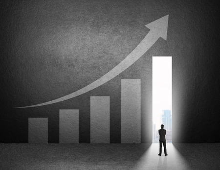 growth arrow: Silhouette of businessman stand in front of the growth chart on the wall.