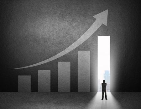 grafica de barras: Silueta de hombre de negocios de pie en frente de la tabla de crecimiento en la pared. Foto de archivo