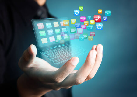 global innovation: Touch screen laptop with colorful application icons in businessman hand