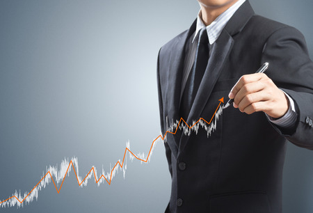 upward graph: Business man drawing a growing graph concept