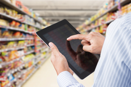manager: Businessman checking inventory in minimart on touchscreen tablet