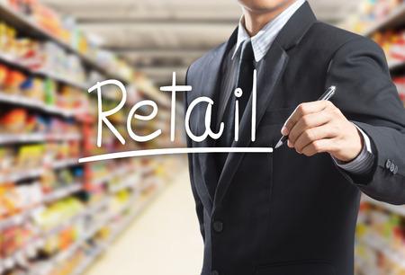 スーパー マーケットで単語小売を書くビジネス男