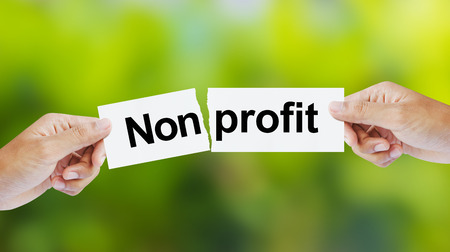 earnings: Businessman tearing the word Nonprofit for Profit Stock Photo