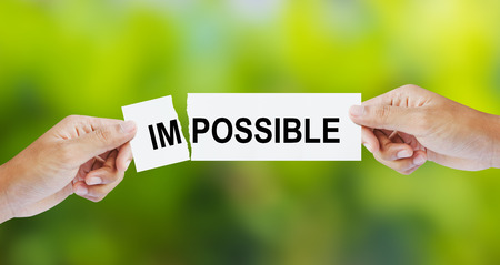 Businessman tearing the word Impossible for Possible Standard-Bild