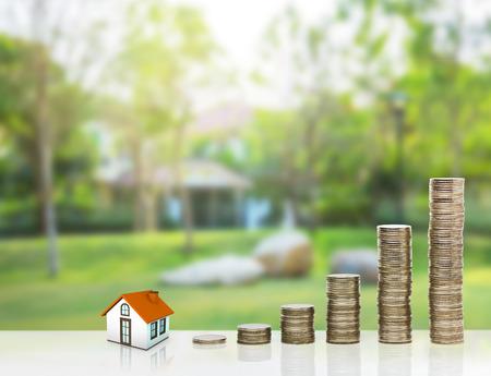 작은 집과 금 스택 동전입니다. 주거 구매의 개념