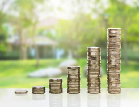 financial cash: Coin stacks arrage growing up on garden and grass background Stock Photo