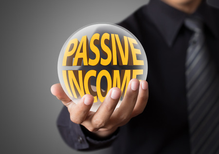 Businessman holding crystal ball with passive income concept photo