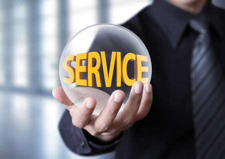 Businessman holding crystal ball with service concept photo