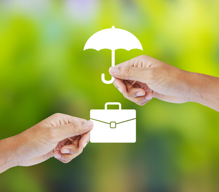financial risk: Business insurance concept with an umbrella covering business briefcase
